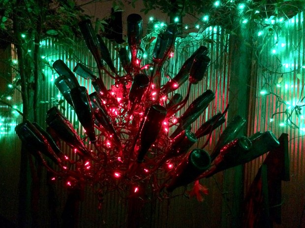 Bottle tree at night with red and green lights