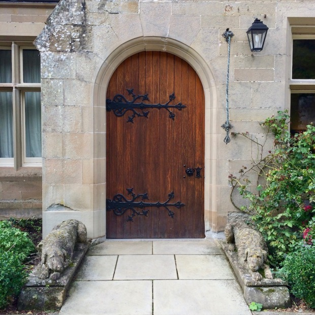 Stone dogs lie on either side of the arched door at Abbotsford