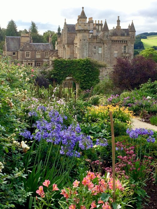 Wide flower borders in front of a castle-like house