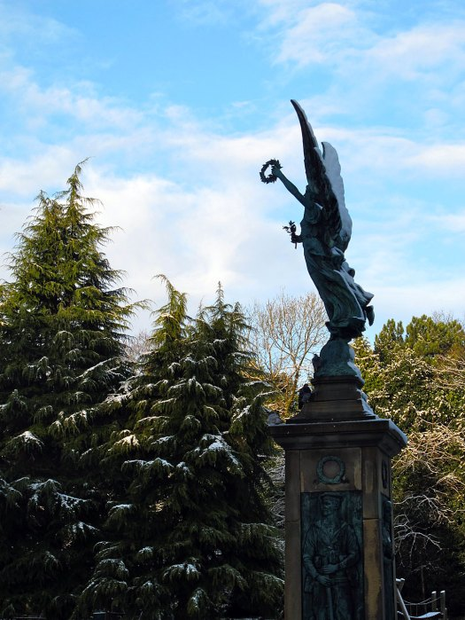War memorial topped by an angel with trees in the background