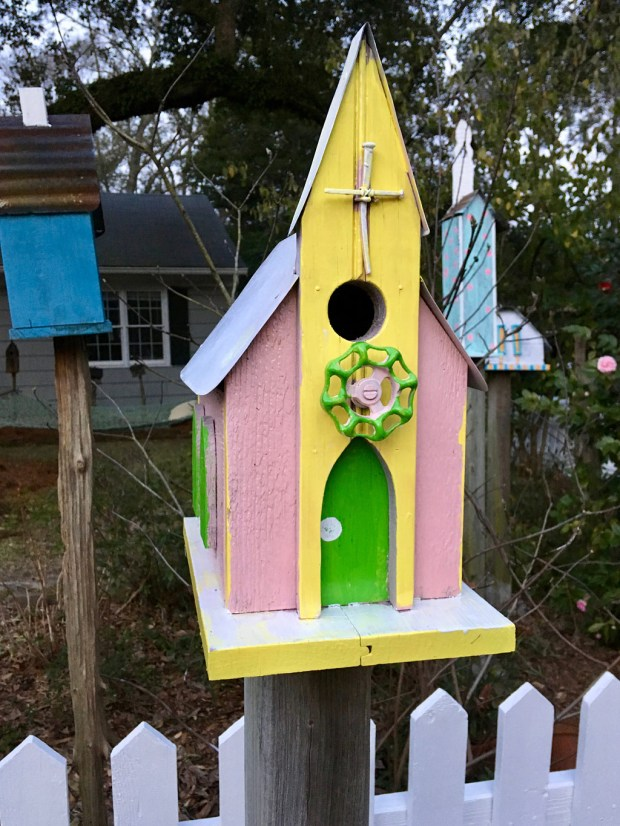 Pink, yellow and lime green birdhouse with a church steeple