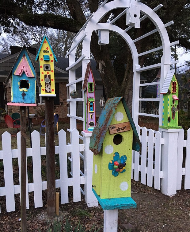 Entryway to home, decorated with five tall birdhouses