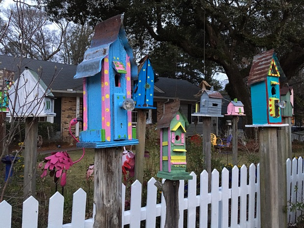 Brightly coloured birdhouses on wooden poles with a white picket fence