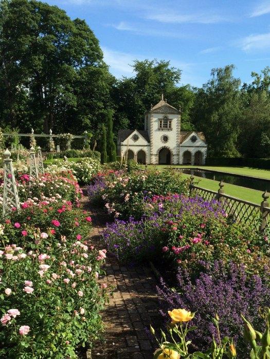 A folly behind a garden of roses and perennials
