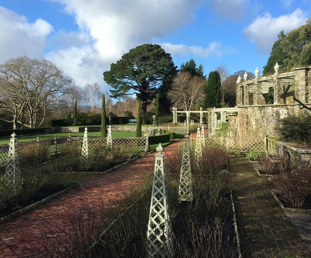 Obelisks and pergolas in a garden of pruned back roses