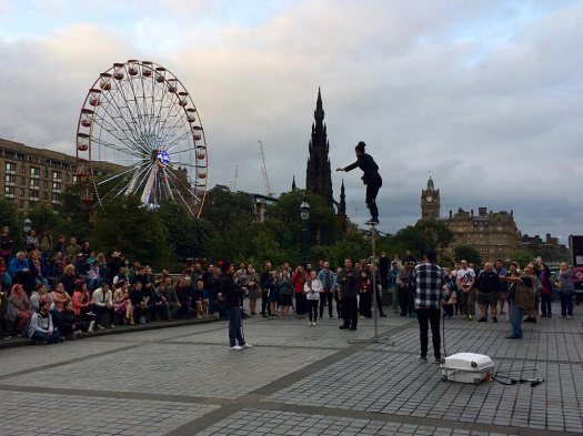 Street entertainer balances on a pole watched by an audience