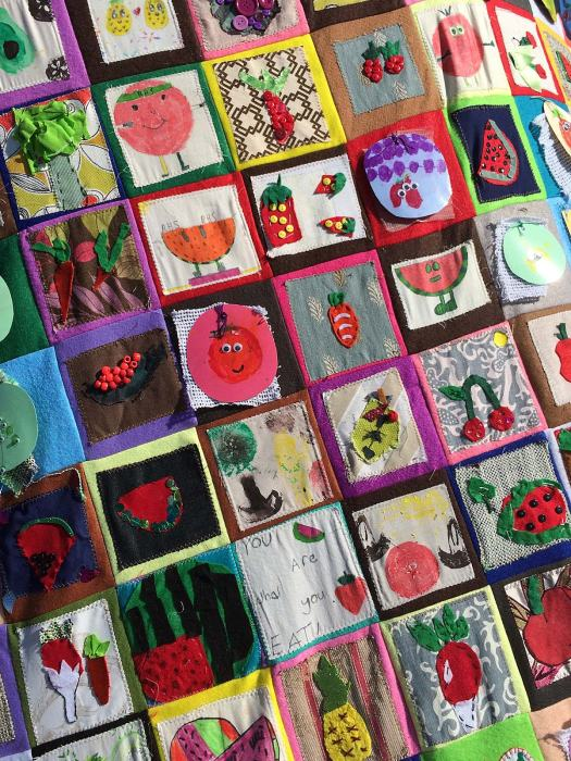 Patchwork throw with smiling fruits drawn by kids