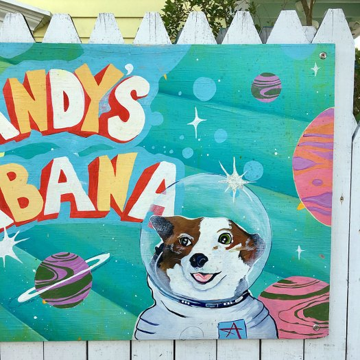 Painting of a dog in a space suit fastened to a picket fence