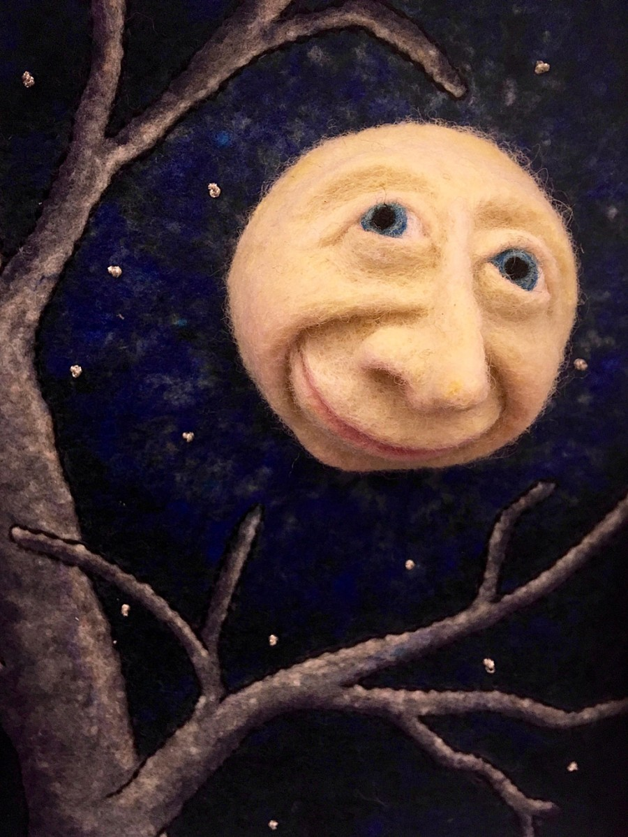A felt man in the moon shines through the branches of a tree
