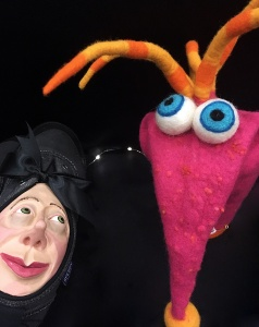 A shoe with a human face and a big-eyed glove puppet