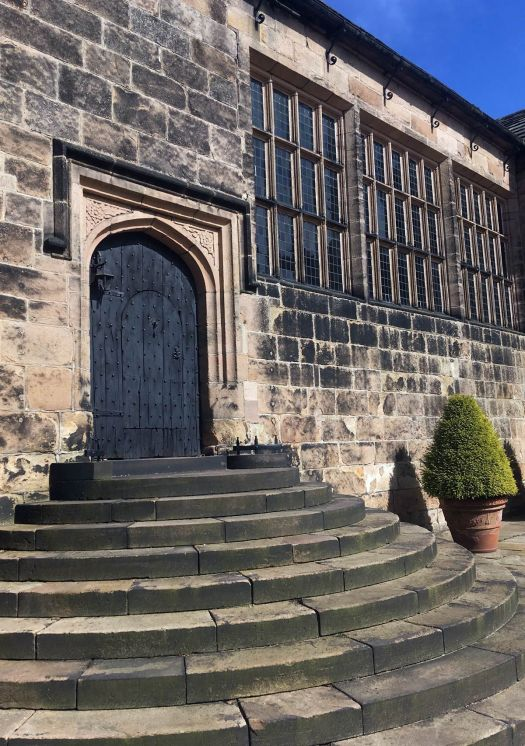 A traditional entrance, with mullioned windows beside a black wooden door