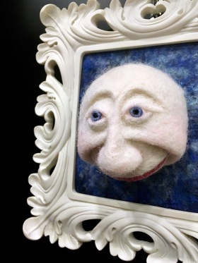 Three dimensional moon face in a white frame