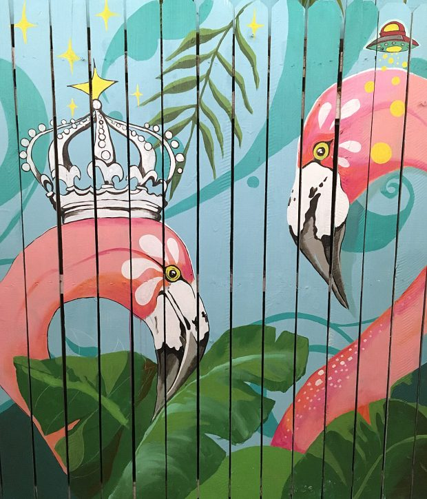 Pink flamingos, one with a crown, painted on a fence
