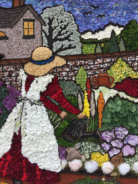 Well dressing: girl in a pinafore watering flowers in a walled garden