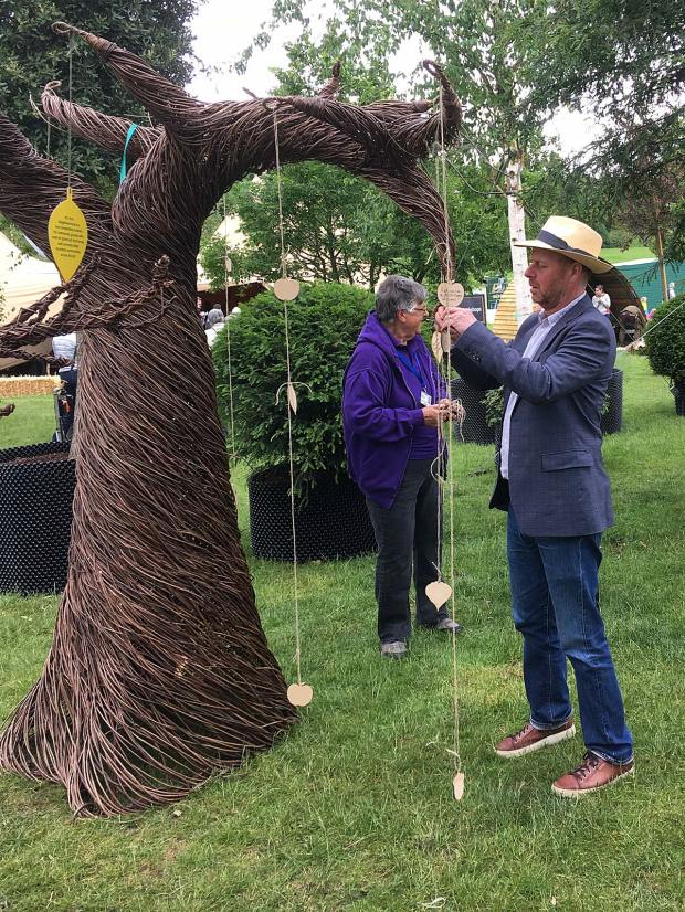 Joe Swift ties a wish to a wicker tree