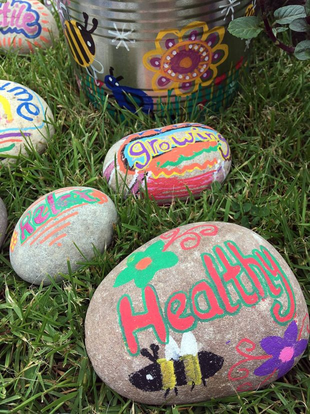 Pebbles painted with the words relax, growing, healthy