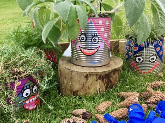 Recycled tin can plant pots with smiling faces painted on