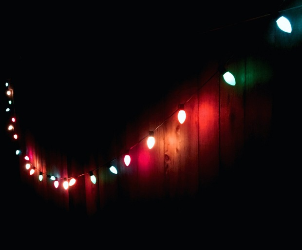 String lights reflect their colours on a fence