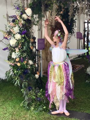 A girl dressed as a fairy in a ballet pose