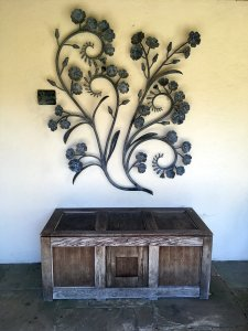 Flower scroll artwork above a rustic trunk at York Gate Garden