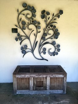 Flower scroll artwork above a rustic trunk at York Gate Garden