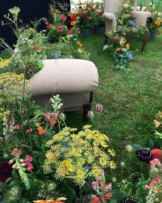 Sneak peek of a floral display with armchairs