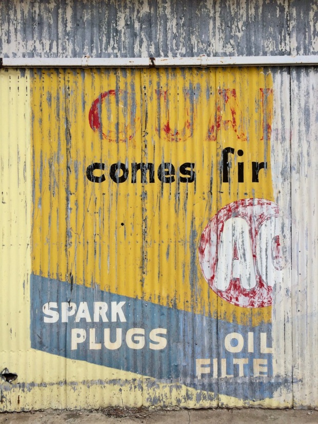 Faded advert on a garage wall