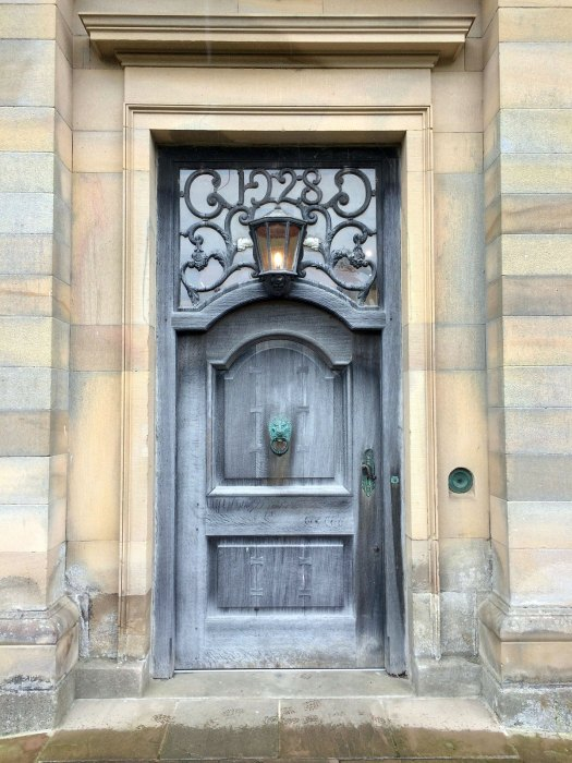 Traditional door with light and ornate knocker at Howick Hall