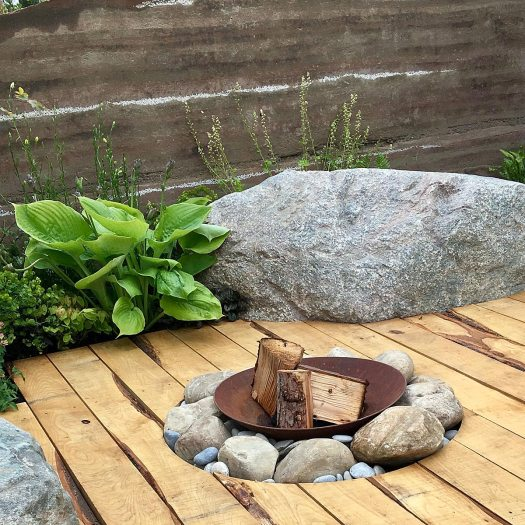 Fire pit, boulder, hosta and sweet chestnut decking