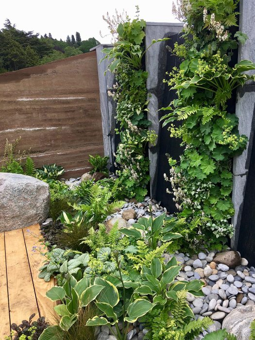 Eutierria Show Garden with rammed wall, pebble mulch, and green water wall