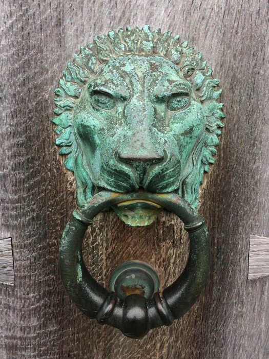 Door knocker held in the mouth of a lion