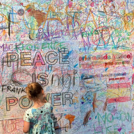 Child drawing on a peace wall at the Double Fantasy exhibition