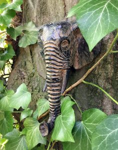 Metal head of an elephant on a tree trunk
