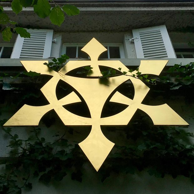 Gold motif under a shuttered window at the Vortex Garden