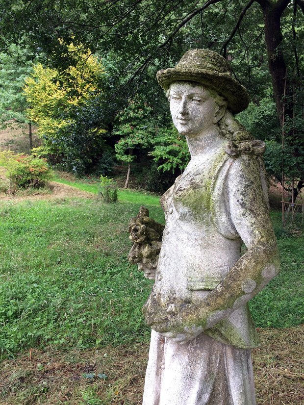 Statue of a lady wearing a hat holding flowers at Gresgarth Gardens