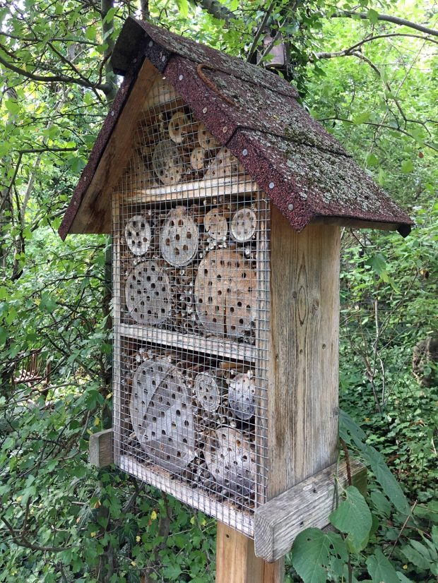 Roofed insect hotel on a wooden post