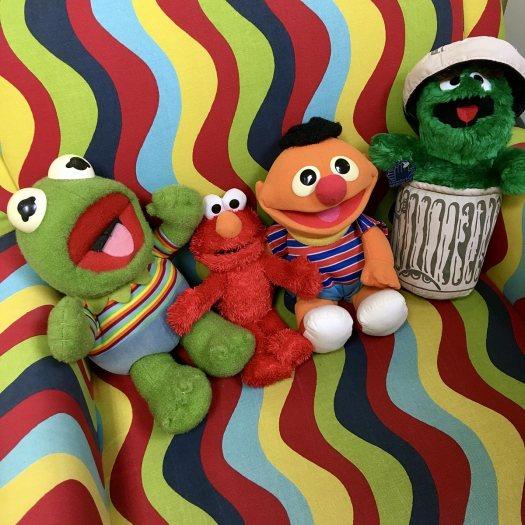 Kermit, Elmo, Ernie, Oscar the Grouch toys on a patterned chair