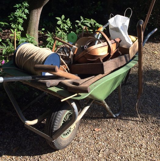 Green wheelbarrow loaded with garden equipment