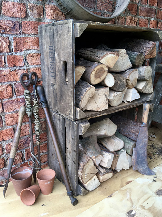 Firewood in wooden crates with old tools