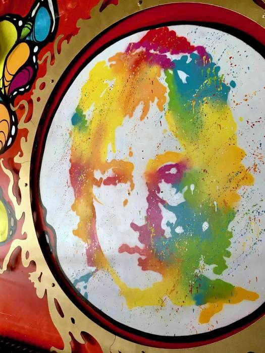 Colourful portrait of John Lennon in a gold frame
