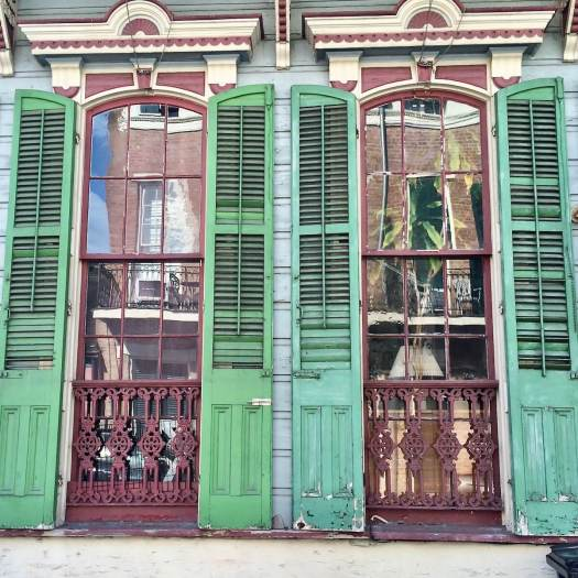 Green exterior shutters on a traditional wooden house