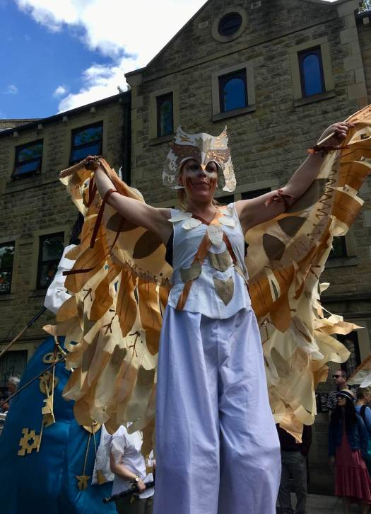 Stilt walker with golden wings