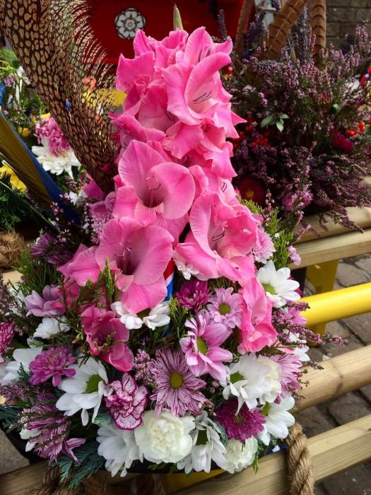 Pink gladioli form a point on a morris hat