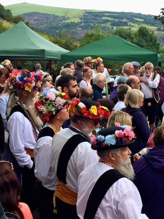Morris dancers wearing flower hats in the Saddleworth Rushcart crowd