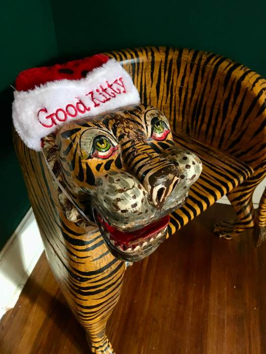 Wooden seat shaped and painted like a tiger with a Good Kitty hat