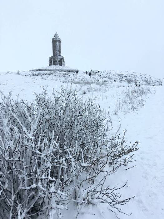 People walking to Darwen Jubilee Tower in the snow