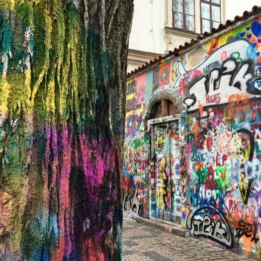 Painted tree trunk with the John Lennon wall, Prague