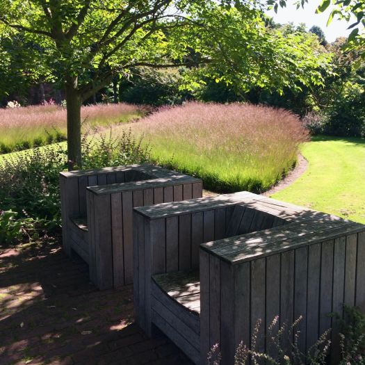 Stylish wooden garden chairs in the shade