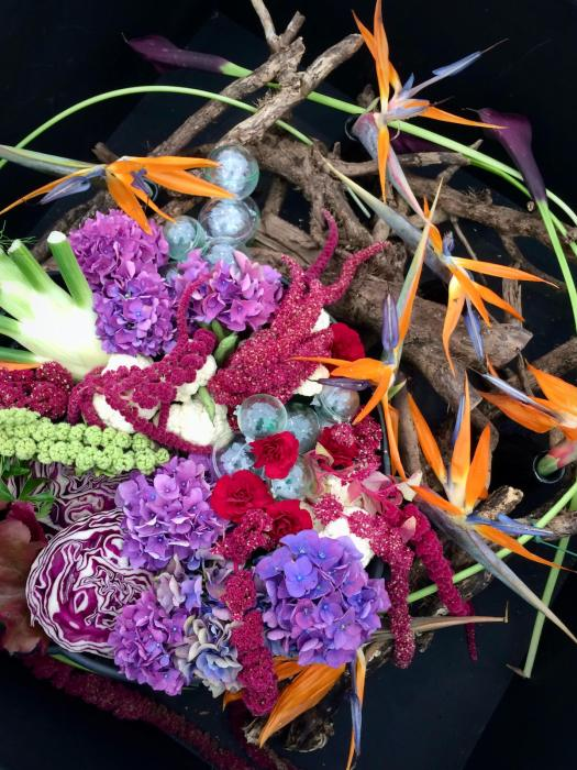 Flower arrangement with cabbages, birds of paradise and branches