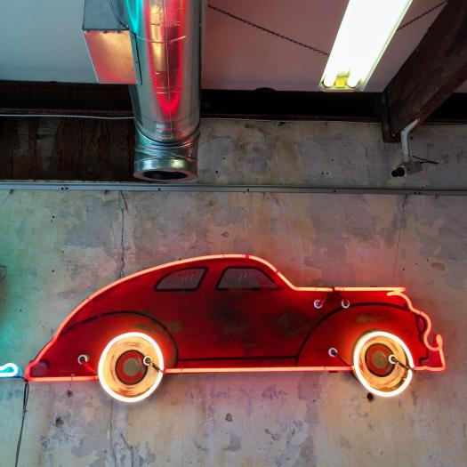 Red neon car hung on an old plaster wall